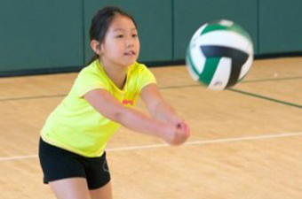 young girl wearing a yellow shirt and black shorts bumps a volleyball