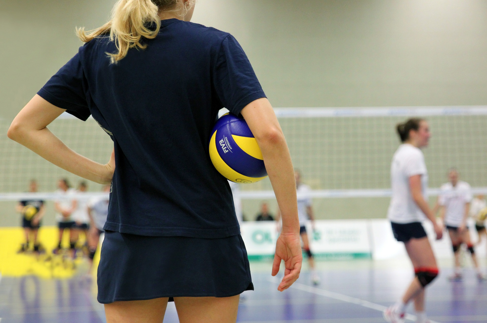 Girl wearing a black shirt holding a volleyball under her arm watching people play volleyball
