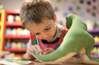 Boy painting a ceramic dinosaur green