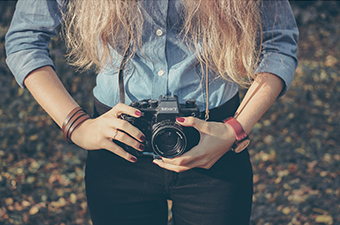 Female photographer wearing a denim shirt and black pants, holding camera at waist level