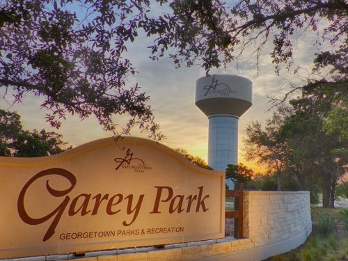 Sun rises on the entry sign for Garey Park in Georgetown, TX with water tower in the background