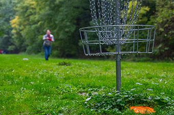 Woman playing disc golf in a park