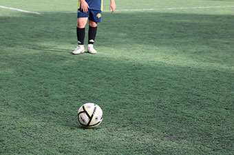 Boy standing behind a soccer ball on a soccer field
