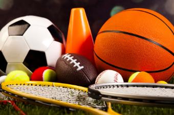 A tennis racket, tennis balls, football, basketball, baseball glove, baseball, baseball bat and soccer ball