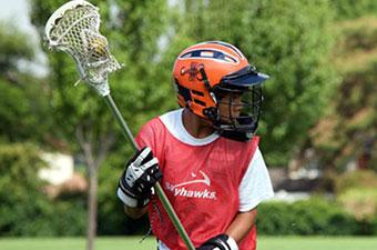 Child playing lacrosse wearing a Skyhawks jersey