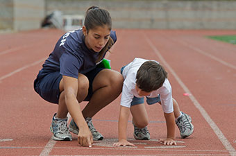 A woman helping a child get ready to run on a track
