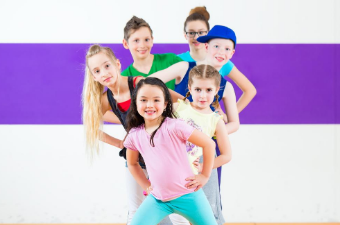 Group of kids in coloring dance outfits posing with their hands on their hips and smiling