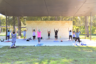 Group of people practicing yoga under the Legacy Pavilion in San Gabriel Park in Georgetown, TX