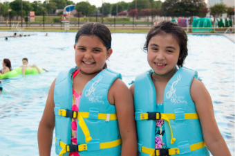 two girls wearing blue lifejackets pose on the side of a swimming pool